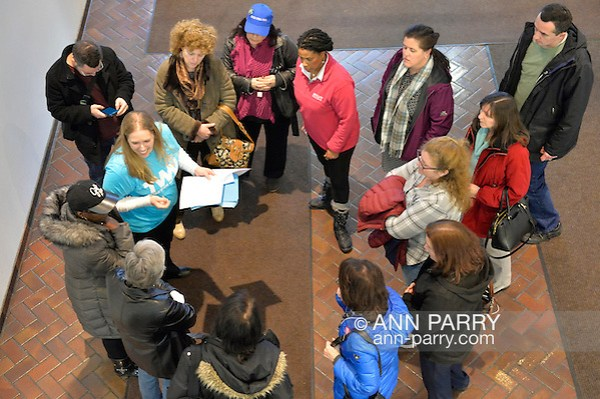 Melville, New York, USA. 24th January 2017. Fourteen members of Together We Will Long Island gather in lobby of bulding that U.S. Senator Chuck Schumer of New York has his Melville office in. They discussed plans before stopping by Schumer's office to share their concerns, especially about Trump's Cabinet appointees, #SwampCabinet. TWWLI members included, clockwise starting left, (in black cap) SHERRY MEDEROS, of Copiague; (in light blue TWWLI shirt) administrator SUE MOLLER of Merrick; social media director JUAN ALICEA, of Medford; member; (in blue cap) ANDREA ROSS BOYLE, of Dix Hills; (in coral sweater) TEDRA GRANT, of Dix Hills; member; (at upper right) PHILIP SOLIS, of Dix Hills; member; (holding coat) ERICA DORAN, of Syosset; LAURIE MITCHEL, of West Babylon; This Stop Trump Tuesday, #StopTrumpTuesday, event was part of nationwide political movement. Members of organizations such as MoveOn, Indivisible, and TWW plan to visit their Senators' offices each Tuesday duringTrump's first 100 days of presidency. (Ann Parry/Ann Parry, ann-parry.com)