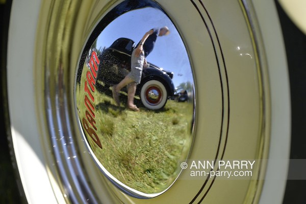 Westbury, New York, USA. June 12, 2016. A yellow 1948 Bantam Roadster, owned by Wade Jacobs of Mineola, has reflection of man walking by nearby vintage black car on its hubcap, at the Antique and Collectible Auto Show at the 50th Annual Spring Meet at Old Westbury Gardens, in the Gold Coast of Long Island, and sponsored by Greater New York Region, GNYR, Antique Automobile Club of America, AACA. Participating vehicles in the judged show included hundreds of domestic and foreign, antique, classic, collectible, and modern cars. (Ann Parry/Ann Parry, ann-parry.com)
