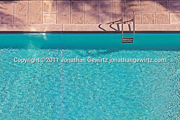 Overhead view of a section of a swimming pool. Bright sunlight on brilliant blue water. (© Jonathan Gewirtz)