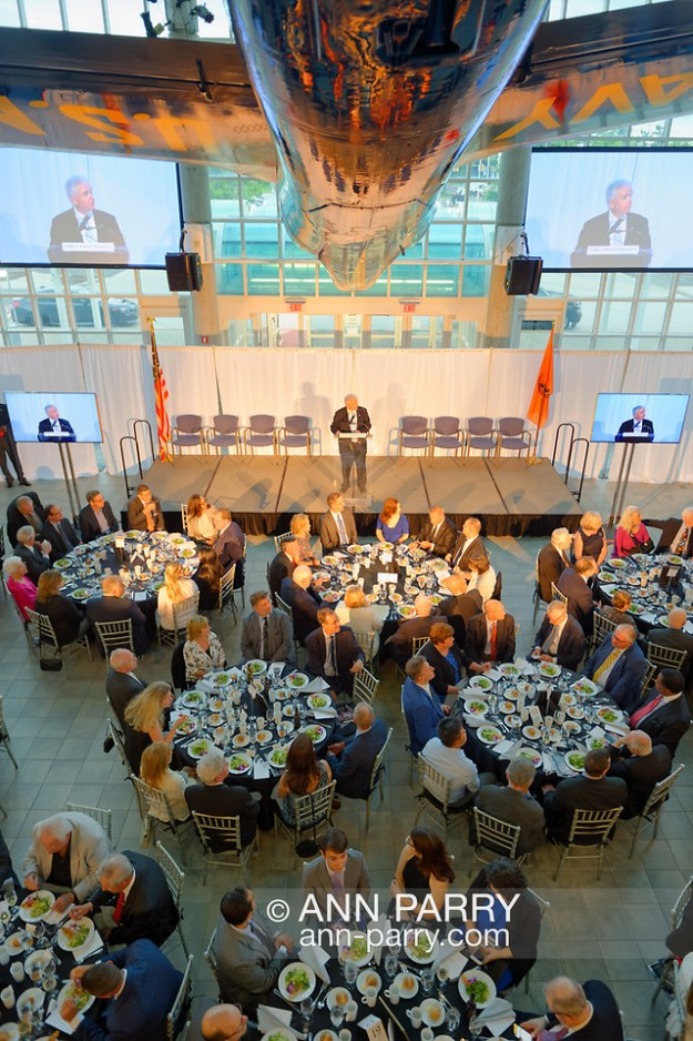 Garden City, New York, U.S. June 6, 2019. ANDY PARTON, President of Cradle of Aviation, is speaking on stage, as seen from second level of atrium of Cradle of Aviation Museum, during Apollo at 50 Anniversary Dinner, an Apollo astronaut tribute celebrating the Apollo 11 mission Moon landing. The 5 Apollo Astronauts, 2 Apollo Flight Commanders, and Nassau County Executive LAURA CURRAN sat at tables next to stage. U.S. Navy Blue Angels Grumman F-11A Tiger jet is suspended from ceiling. (Ann Parry/Ann Parry, ann-parry.com)