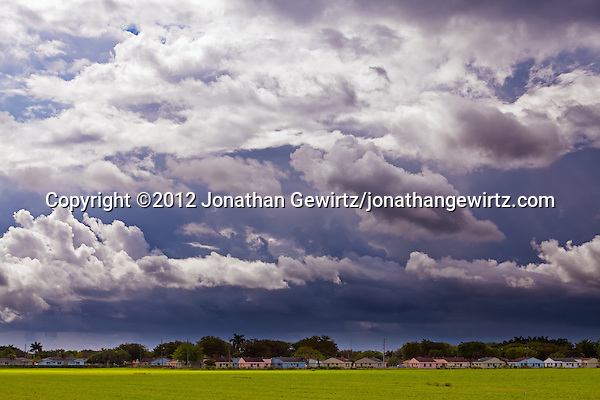 A dramatic sky of dark rain clouds contrasts with colorful houses and green fields near Ingraham Highway in Homestead, Florida. (© 2012 Jonathan Gewirtz / jonathan@gewirtz.net)
