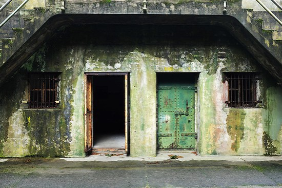 Open and closed rusty green steel doors in concrete bunker tunnels, Artillery Hill, Fort Warden State Park, Port Townsend, Washington, USA (Brad Mitchell)