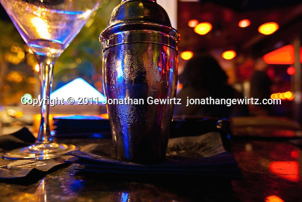 A stainless steel cocktail shaker and drink glass on a restaurant table under subdued colorful light.. (© Jonathan Gewirtz, jonathan@gewirtz.net)