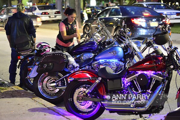 Bellmore, New York, USA. 11th August 2017. Motorcyclist locks up her parked Harley Davidson motorcycle parked with other motorcycles across the street from Bellmore Friday Night Car Show, in parking lot of LIRR Bellmore station. (Ann Parry/Ann-Parry.com)
