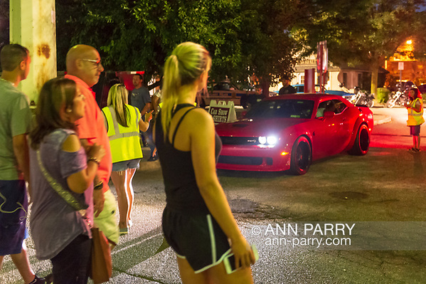 Bellmore, New York, USA. August 24, 2018. Members of Chamber of Commerce of the Bellmores, wearing yellow reflective safety vests, give drivers a car sticker after they collect $3 entrance fee from each car entering the Bellmore Friday Night Car Show at the Bellmore LIRR Train Station parking lot. Visitors walk in for free. (Ann Parry/Ann Parry, ann-parry.com)