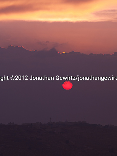 A hazy red sun rises over the Mountains of Moab behind the village of Abu Dis on the eastern outskirts of Jerusalem. (© 2012 Jonathan Gewirtz / jonathan@gewirtz.net)