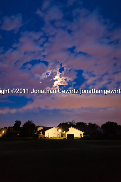 The full moon is hidden by a partly cloudy sky over homes on a Davie, Florida golf course. (Jonathan Gewirtz)