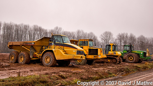 Some Cat's (and a John Deere) parked in the mud on a misty winter day. There used to be trees here, soon to become a housing tract. Image taken with a Nikon D2xs camera and a new 12-24 mm f/4 DX lens (ISO 100, 24 mm, f/4, 1/200 sec). (David J Mathre)