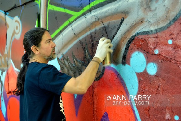 Huntington, New York, U.S. 24th August 2013. SONIC BAD, legendary street artist JESSE RODRIGUEZ from the Bronx, graffiti painting wall on the back of Huntington Arts Council building, during art event Off the Wall Block Party, by SPARKBOOM. (Ann Parry/nn-parry.com)