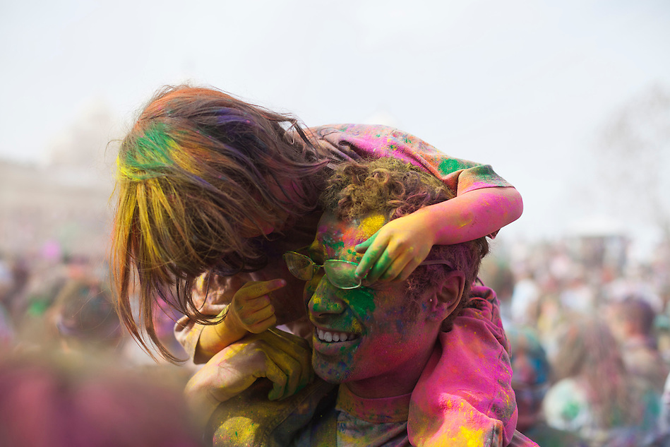 After a young girl throws green powder in his dad?s face, she realizes its in his eyes and tries to help him while he remains smiling and in good sprits at the Holi Festival of Colors, on Saturday, Mar. 24, 2012, at the Lotus Temple, in Spanish Fork, Utah. (Photo by Benjamin B. Morris ©2012) (Benjamin B. Morris)