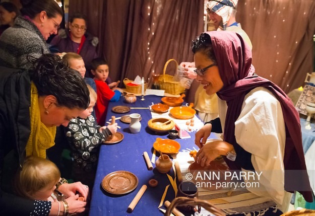 Garden City, New York, USA. December 6, 2013. Visitors experience the nativity scene at the manger, with Mary, Joseph, and baby Jesus, the Holy Family, at A Night in Bethlehem, an annual Advent at the Lutheran Church of the Resurrection, on Long Island, on December 6, 7, and 8. (Ann Parry/ann-parry.com)