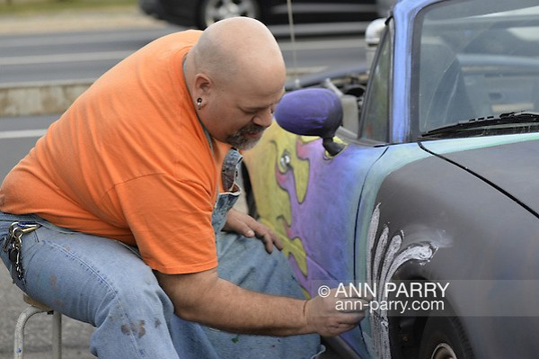 Bellmore, New York, USA. May 29, 2015. PHIL ZIRKULI, a Baldwin Art Teacher, is free-hand drawing colorful designs with chalk paint on his black 1992 Mazda Convertible at the Friday Night Car Show held at the Bellmore Long Island Railroad Station Parking Lot. Zirkuli explained he decorates his car to draw attention to the importance of art education. Hundreds of classic, antique, and custom cars are generally on view at the free weekly show, sponsored by the Chamber of Commerce of the Bellmores, from May to early October. (Ann Parry/Ann Parry, ann-parry.com)