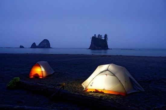 Glowing tents camping on beach below sea stack on Washington Coast, Scotts Bluff, South Coast Trail, Olympic National Park, Washington, USA (Brad Mitchell Photography)