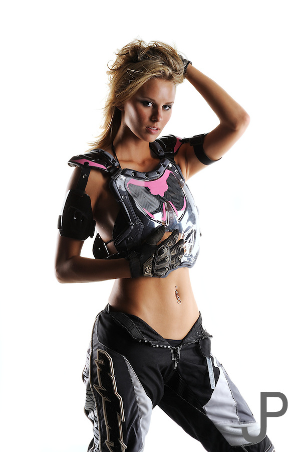 Beautiful sexy blond female in motocross riding gear on white background.  No logos, model released. (James Pratt)
