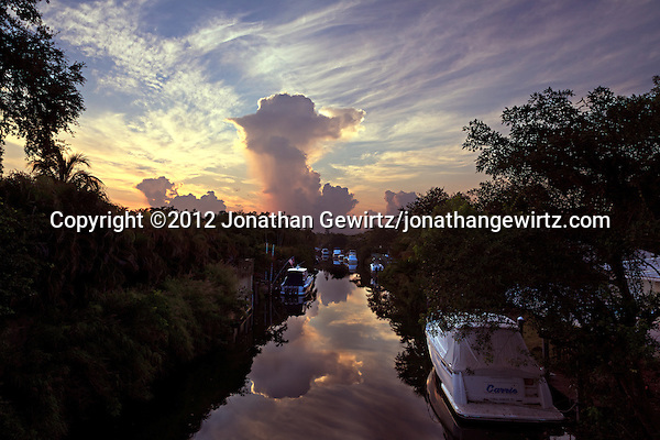 A dissipating thunderstorm reflects from the tranquil surface of a canal shortly after sunrise in Coral Gables, Florida. (© 2012 Jonathan Gewirtz / jonathan@gewirtz.net)
