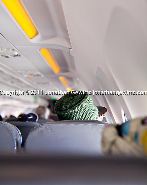 Rastafarian hat wearer sitting a few rows ahead of the camera on a plane. (Jonathan Gewirtz)