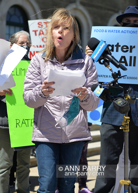 """Mineola, NY, USA. April 26, 2021. AGATHA NADEL, Director of North Shore Concerned Citizens (NSCC) speaks at rally, and behind her at right is ERIC WELTMAN, Senior Organizer for Food & Water Watch and Food & Water Action. Faced with a 26% rate increase from New York American Water going into effect May 1, 2021, activists and residents who are NYAW customers rally to urge NYS Assembly to push through legislation, before then, corresponding with NYS Senate Bill S989A to establish a Nassau County Water Authority. (© 2021 Ann Parry/AnnParry.com)"
