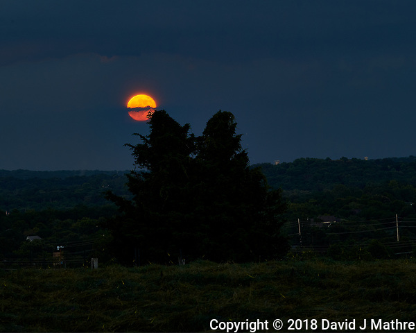 Strawberry Full Moon Rising Through the Clouds over Montgomery Township. Image taken with a Nikon D5 camera and 70-200 mm f/2.8 VR lens (ISO 100, 200 mm, f/11, 6 sec). Raw image processed with Capture One Pro. (David J Mathre)
