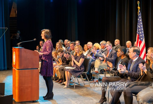"""Hempstead, NY, U.S. January 1, 2018. SYLVIA CABANA, at podium, speaks after being sworn in as Hempstead Town Clerk, and LAURA GILLEN, just sworn in as Hempstead Town Supervisor, sits at left in front row with family, at Hofstra University. (© 2018 Ann Parry/Ann-Parry.com)"