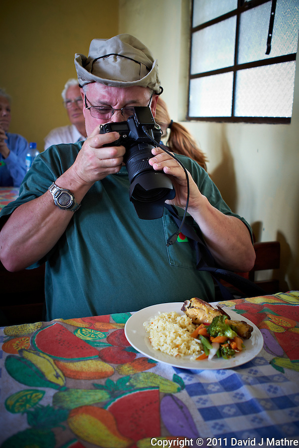 Rob Documenting his Lunch in San Francisco de Sales.  Pacaya Volcano National Park. Image taken with a Leica X1 (ISO 200, 24 mm, f/2.8, 1/30 sec). Raw image processed with Capture One Pro and Photoshop CS5. . (David J Mathre)