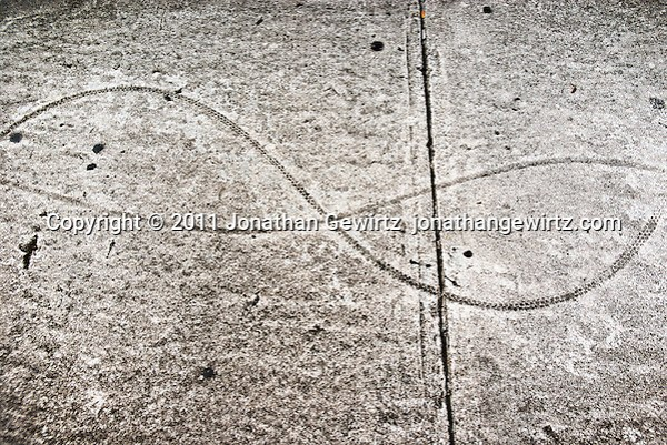 Undulating bicycle tire tracks on a concrete sidewalk. (© Jonathan Gewirtz)