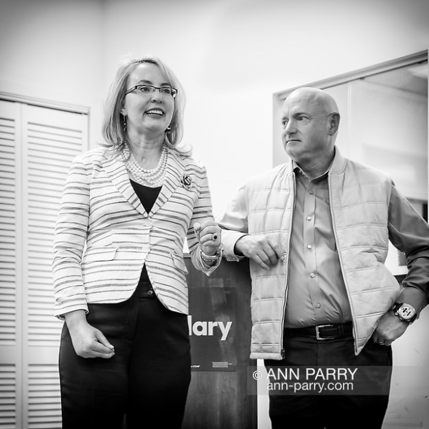 """Garden City, New York, USA. April 17, 2016. GABBY GIFFORDS, former United States Congresswoman - as her husband MARK KELLY, former NASA astronaut looks on - speaks about the importance of GOTV, Getting Out The Vote for Hillary Clinton - including because of Clinton's strong position on stricter gun control legislation - at the Canvass Kickoff at the Nassau County Democratic Office in Garden City. Giffords survived an assassination attempt near Tuscon, Arizona, during her first'Congress on Your Corner' event in January 2011. Kelly was a NASA astronaut. (© 2018 Ann Parry/AnnParry.com)"