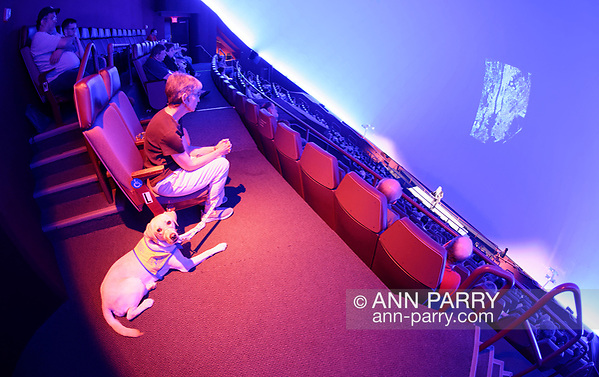 Garden City, NY, USA. June 21, 2018. Space Shuttle Astronaut MIKE MASSIMINO gives lecture in JetBlue Sky Theater Planetarium at Cradle of Aviation Museum. Volunteer puppy raiser FLORENCE SCARINCI is seated next to dog she's training from Canine Companions for Independence, a Medford non-profit. (© 2018 Ann Parry/Ann-Parry.com)