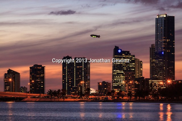 A Goodyear blimp flies behind buildings on Miami's Brickell Avenue at dusk with the Rickenbacker Causeway in the foreground. (Jonathan Gewirtz   jonathan@gewirtz.net)