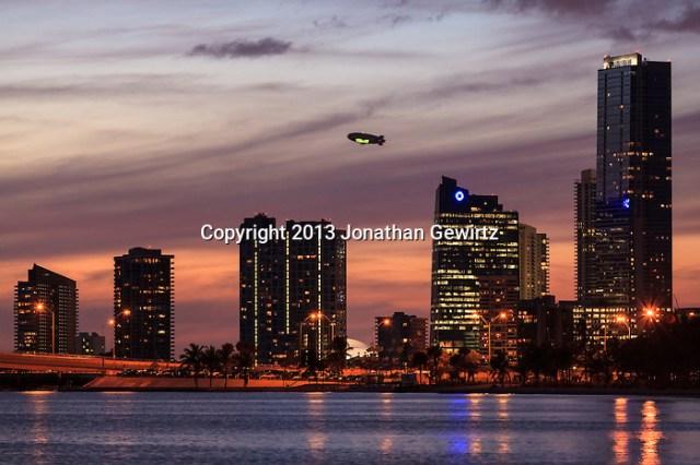 A Goodyear blimp flies behind buildings on Miami's Brickell Avenue at dusk with the Rickenbacker Causeway in the foreground. (Jonathan Gewirtz   jonathan@gewirtz.net)