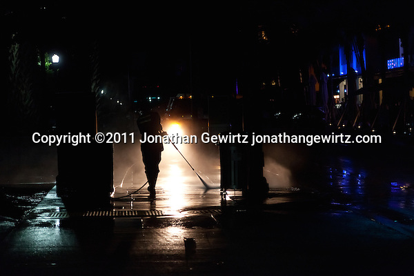 A Miami Beach municipal employee pressure washes the sidewalk during early morning hours. (Copyright 2011 Jonathan Gewirtz jonathan@gewirtz.net)