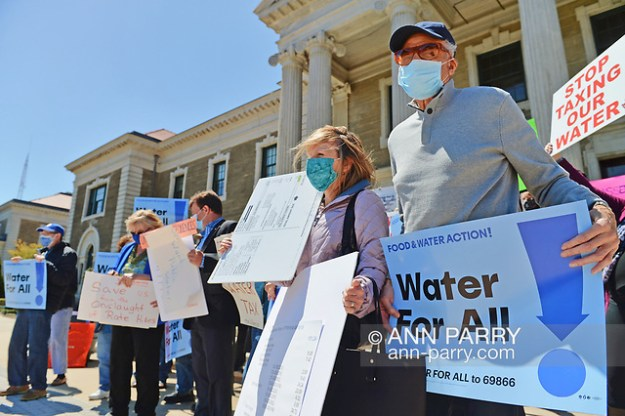 """Mineola, NY, USA. April 26, 2021. At rally, activists hold signs saying STOP TAXING OUR WATER, and Water for ALL! Faced with a 26% rate increase from New York American Water going into effect May 1, 2021, activists and residents who are NYAW customers rally. (© 2021 Ann Parry/AnnParry.com)"