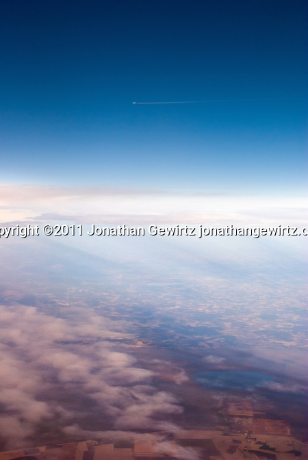 A distant jet aircraft with a contrail flies over a winter landscape. (Jonathan Gewirtz)