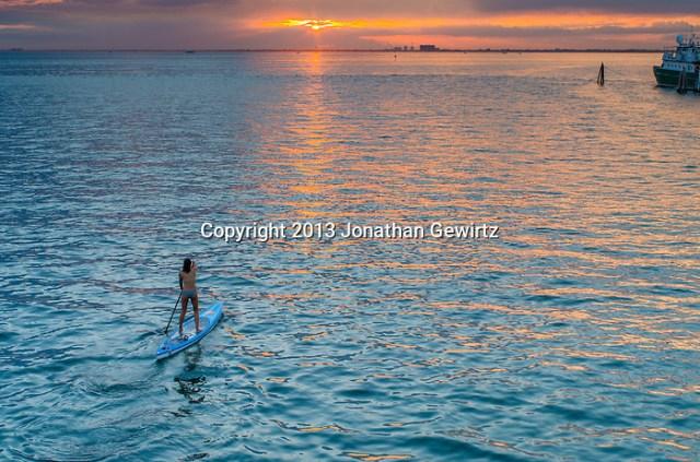 A young woman paddles toward the setting sun in Bear Cut between Virginia Key and Key Biscayne, Florida. (Jonathan Gewirtz Jonathan.Gewirtz@gmail.com)