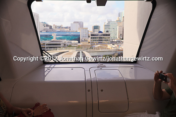 Tourists enjoy a ride in an automated Miami Metromover rail car as downtown Miami's shopping and commercial district looms in the car's front window. (© 2012 Jonathan Gewirtz / jonathan@gewirtz.net)