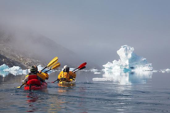 Sea kayakers paddling among icebergs on Sermilik Fjord near settlement of Tiniteqilaq, East Greenland (Brad Mitchell)