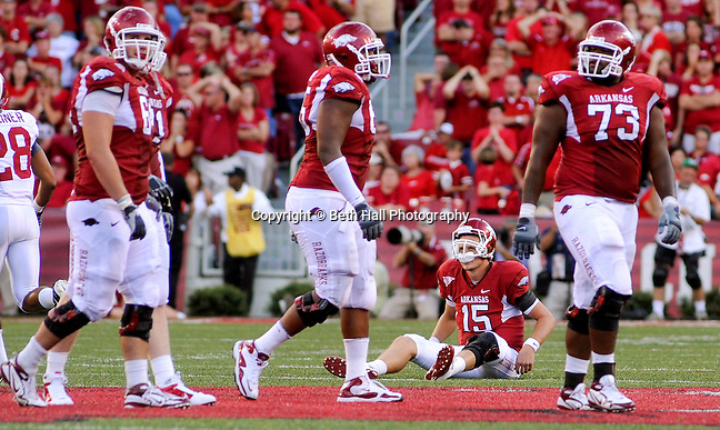 Arkansas quarterback Ryan Mallett (15) sits on the field after throwing an interception during the fourth quarter of the NCAA college football game with Alabama Saturday, Sept. 25, 2010, as teammates center Travis Swanson, far left, tackle DeMarcus Love and tackle Ray Dominguez (73), walk past. Alabama defeated Arkansas 24-20. (Beth Hall)