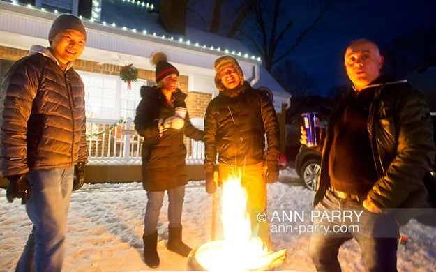 """North Merrick, NY, U.S. Dec. 19, 2020. At center, L-R, JESSICA MACK and JOSH MACK stand with 2 neighbors around fire pit during Community Holiday Tree Walk. (© 2020 Ann Parry/Ann-Parry.com)"