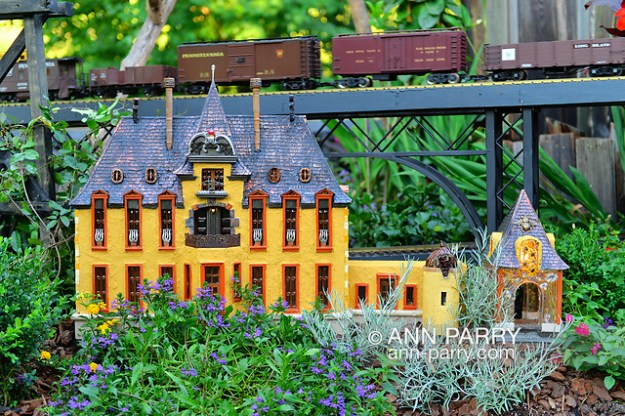 Old Westbury, New York, U.S. June 23, 2021. Old Westbury Gardens has an opening reception for its Great Pine Railway outdoor model train exhibit. The orange Oheka Castle, of Huntington, is one of several Long Island landmarks Leslie Salka Inc created for the unique large G gauge model railroad exhibit, which runs until September 6. (© 2021 Ann Parry/AnnParry.com)