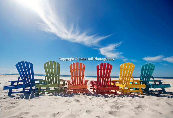 A row of colorful Adirondack lounge chairs lined up on the beach under a blue sky. (Beth Hall)