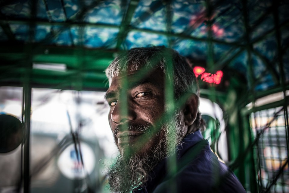 A CNG driver in Dhaka, Bangladesh takes a quick glance at his passengers during a nasty traffic jam. (Paul Ratje)
