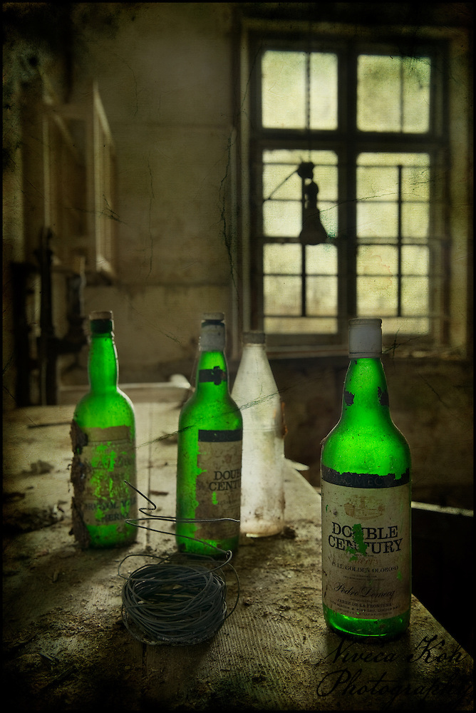Green bottles in an the kitchen of an abandoned house (Viveca Koh)
