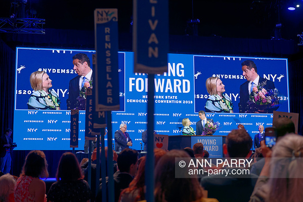 Hempstead, NY, USA. May 23, 2018. HILLARY CLINTON and Governor ANDREW CUOMO, holding bouquet for Clinton, are together on stage during Day 1 of New York State Democratic Convention, held at Hofstra University. (© 2018 Ann Parry/Ann-Parry.com)