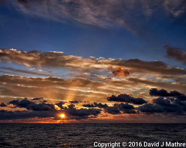 Sunrise, sunburst, crepuscular rays, and clouds over the Pacific Ocean from the aft deck of the MV World Odyssey. Image taken with a Fuji X-T1 camera and 23 mm f/1.4 lens (ISO 200, 23 mm, f/16, 1/60 sec). Raw image processed with Capture One Pro. (David J Mathre)
