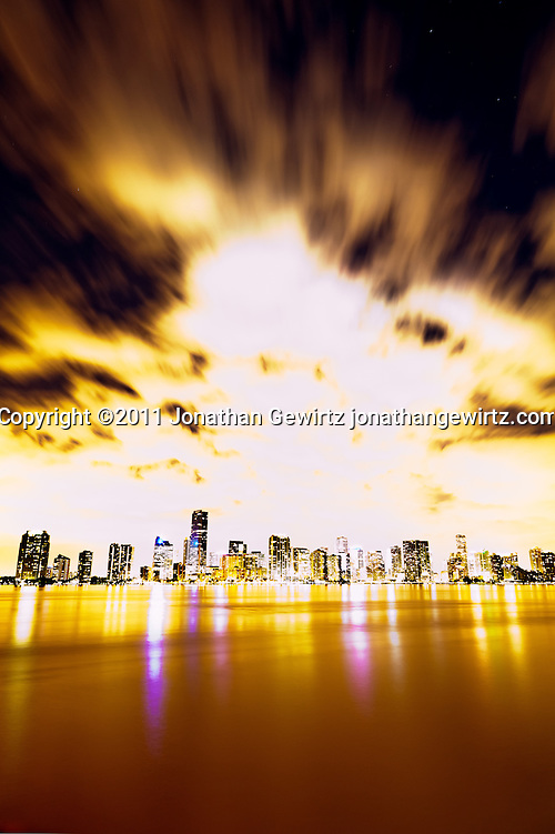 Overexposed view of the downtown Miami bayfront at night, showing hotels, condos and office buildings. (© Jonathan Gewirtz)