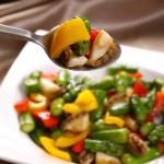 アスパラガスと3色のコショウの炒めあわびをスプーンですくいあげる・ダウンロード可能なグルメ写真素材