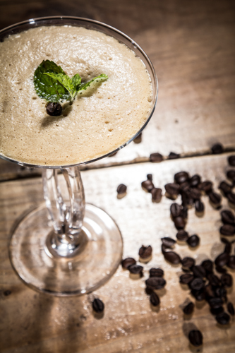 A tall glass of frothy ice coffee with mint leaves