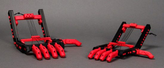 """Snap-Together Robohand by MakerBot: """"A Robohand is a set of mechanical fingers that open and close to grasp things based on the motion of the wrist. When the wrist folds and contracts, the cables attaching the fingers to the base structure cause the fingers to curl. Nearly all the parts of a Robohand are 3D printed on MakerBot Replicator 2 Desktop 3D printers."""""""