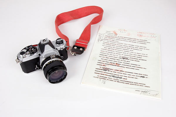 Associated Press reporter Peter Arnett carried this Nikon camera while covering Vietnam. South Vietnamese officials censored this 1963 battlefield report written by Arnett. (Photo: Amy Joseph/Newseum; Camera and report: Gift, Peter Arnett)
