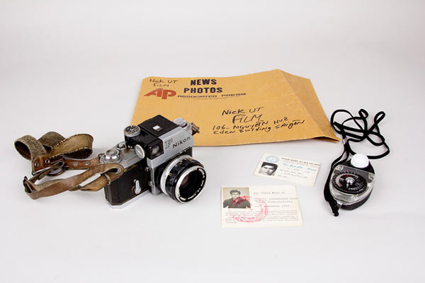 Photographer Nick Ut used this Nikon camera, light meter and envelope while covering Vietnam for the Associated Press. He also carried these press passes. (Photo: Amy Joseph/Newseum; Camera, film envelope, press passes and light meter: Loan, Nick Ut)