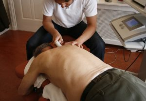 Physiotherapist treats senior patient on painful shoulder
